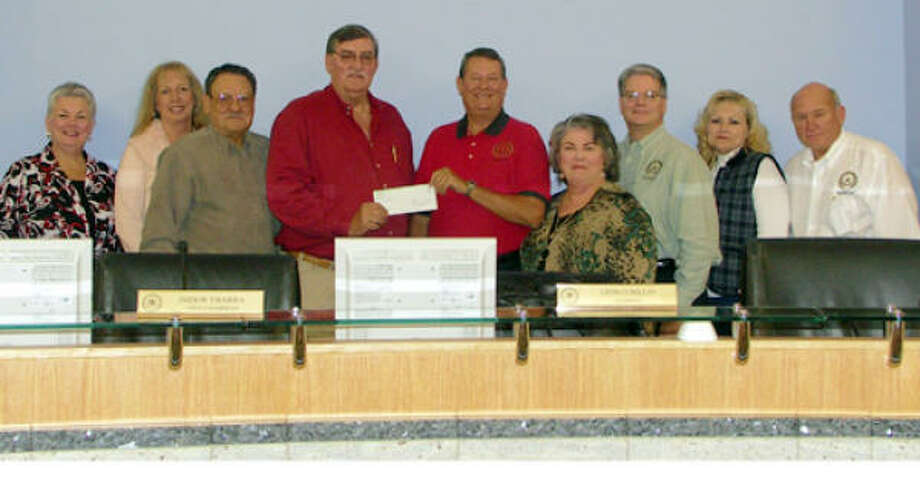 The East Montgomery County Improvement District board of directors presented Montgomery County Precinct 4 Commissioner Ed Rinehart with a $40,000 check at last Thursday evening's meeting which will be used to help fund a litter abatement program within the district. From left to right are directors Connie Bloodworth, Sue Rinehart and Isidor Ybarra, Precinct 4 Commissioner Ed Rinehart, EMCID board of directors chairman Leon Cubillass, director Linda Floyd, EMCID president/CEO Frank McCrady, directors Vicky Thuman and Leonard Rogers. Photo: Suzanne West