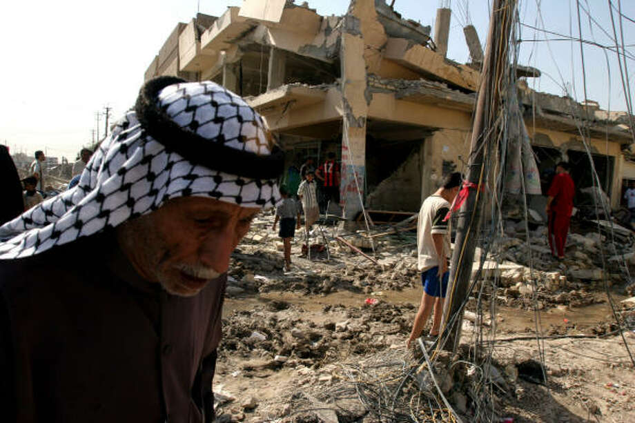 An elderly Iraqi man walks past houses damaged last month in a rocket attack on a predominately Shiite neighborhood in Baghdad, Iraq.Baghdad was once a city where people mixed freely in most parts of town and no one cared if Sunni or Shiite dominated. Photo: KARIM KADIM, AP
