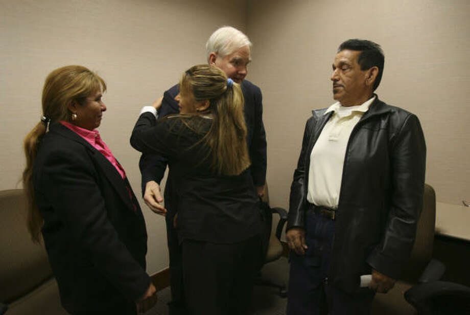 Gracie Amezquita hugs her brother's attorney, Roland B. Moore III, as she and her parents, Maria and Ramiro, celebrate Gilbert Amezquita's impending release Thursday. Photo: KAREN WARREN, Chronicle