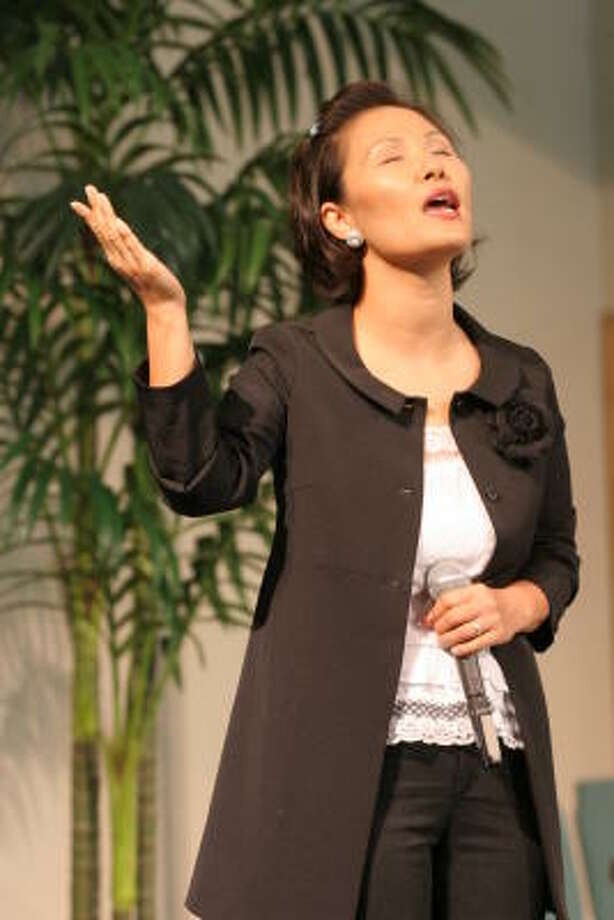 Vicki Sim, wife of Houston Fellowship Church pastor Timothy Sim, sings with the congregation. Photo: Suzanne Rehak, For The Chronicle