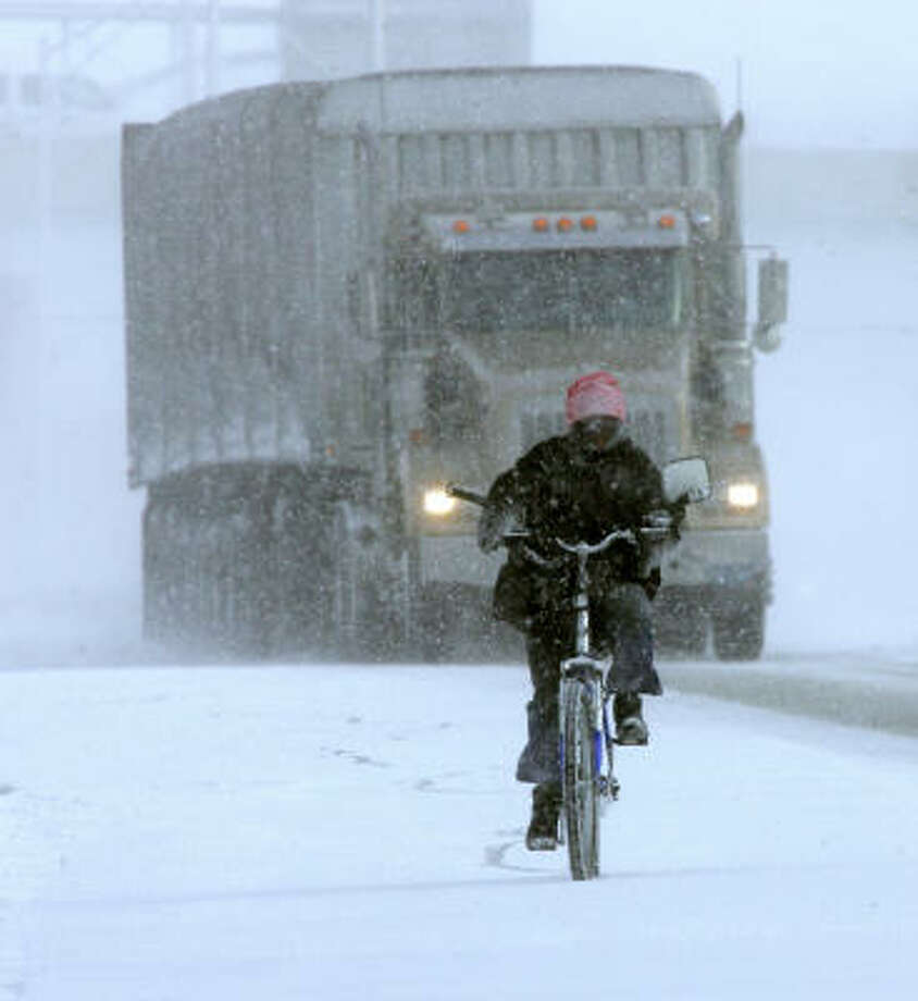David Gilchrist, 50, of South Bend, Ind., battles the blinding snow and traffic along U.S. 20 to run an errand Thursday. Forecasts called for 18 degrees and more snow showers. Photo: JIM RIDER, South Bend Tribune