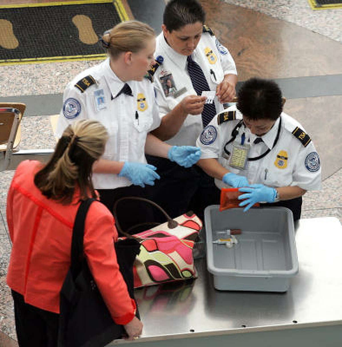 Security screeners remove liquid items from a passenger's luggage Sunday at Denver International Airport. The TSA said changes it made Sunday were based on feedback from security officers and the public.