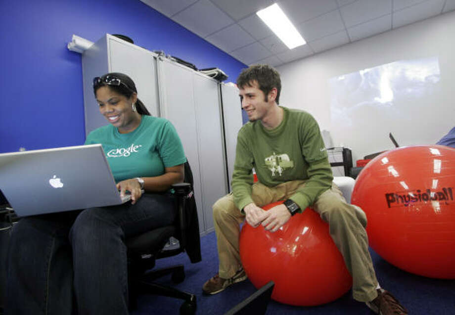 Google employees Erica Baker, left, and Raiford Storey work in the company's new office in Manhattan, which houses 500 workers. Photo: MARK LENNIHAN, AP