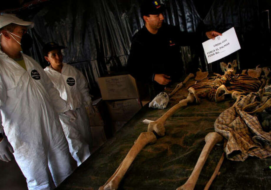 Members of the Colombian Attorney General's Office work on the remains of an unidentified person believed to have been executed by a right-wing paramilitary group in a cattle ranch close to San Onofre in northern Sucre state in May 2005. Photo: Marcelo Salinas, Chronicle File