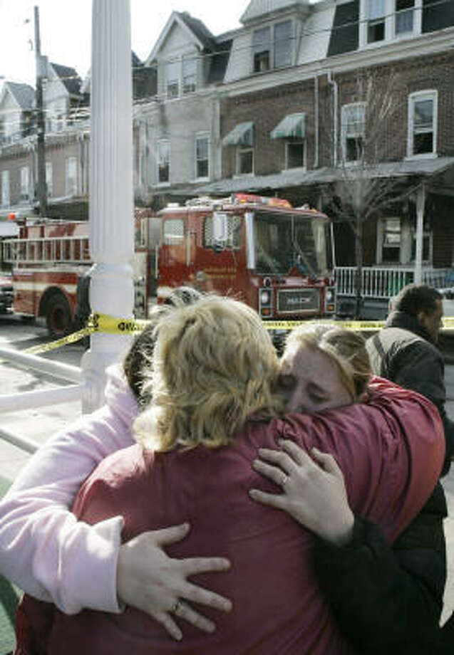 Cindy Gaffney, left, Brenda Pun and Tonya Ebner try to console each other in Allentown, Pa., on Friday after learning their friends had died in the rowhouse fire. Eight other people were injured. Photo: Matt Rourke, AP