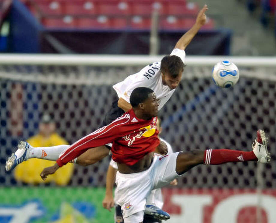 Dynamo defender Eddie Robinson, top, battles Red Bulls' forward Edson Buddle for control of the ball during first-half action Saturday night at Giants Stadium. Photo: BILL KOSTROUN, ASSOCIATED PRESS