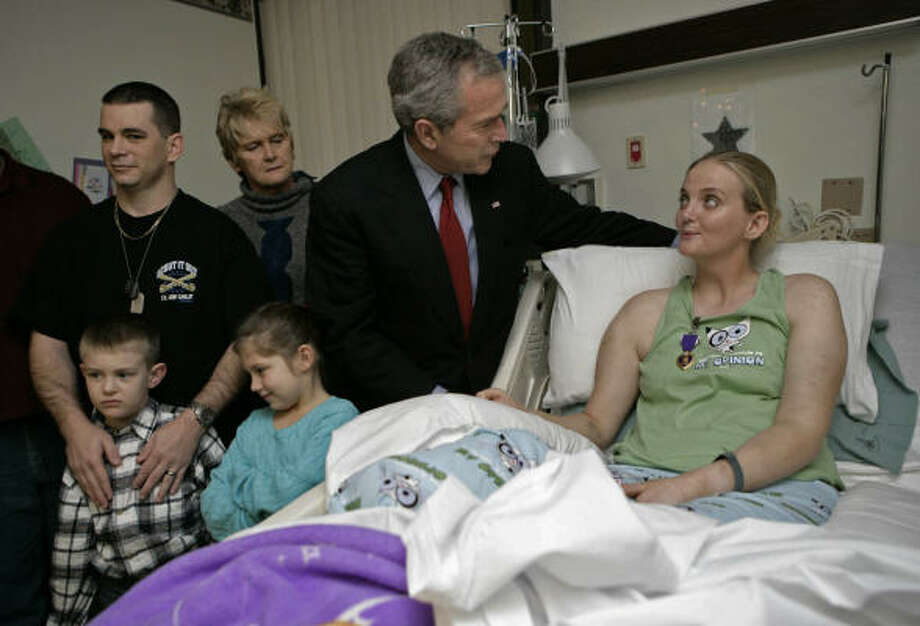 President Bush presents a Purple Heart to Army Spc. Sue Downes while visiting her and other wounded troops at Walter Reed Army Medical Center. Joining in the presentation to the Iowa City, Iowa, private is her husband, Gabriel, left, their son, Austin, daughter Alexis, and Downes' mother, Faye Partin. Photo: ERIC DRAPER, WHITE HOUSE