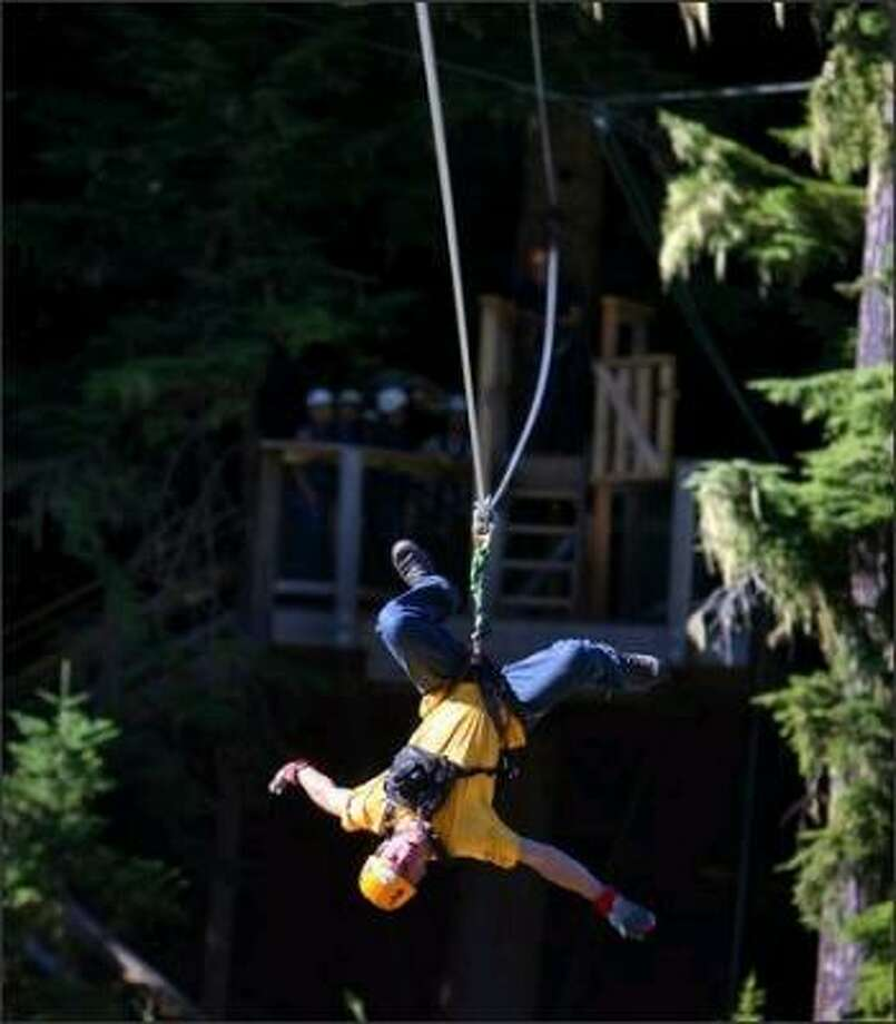 Guide Dave Vest shows his groups some of the ways to ride the zipline as he goes upside down on one of the five different zip runs on the Bear course. Photo: Scott Eklund, Seattle Post-Intelligencer
