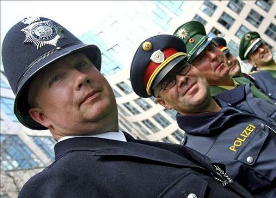 (From L) Policemen from England, Austria and Germany pose for a picture 06 June 2006 at the German Interior Ministry in Berlin. More than 300 foreign policemen from 13 European countries arrived to support German police.  The World Cup kicks off next Friday in Munich with the final in Berlin on July 9. AFP PHOTO / DDP / MICHAEL KAPPELER Photo: MICHAEL KAPPELER, AFP