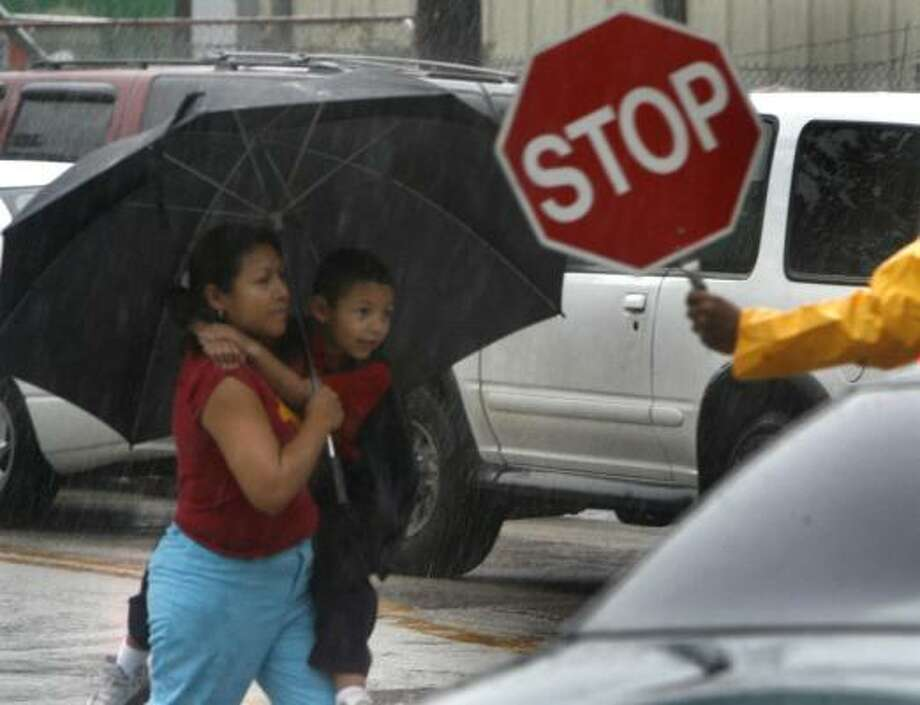 Maria Ponce picks up her son, Kevin Montelongo, 5, from Lantrip Elementary School near downtown Houston during a heavy rain. Many schools canceled classes or let students leave early. Photo: Carlos Antonio Rios, Chronicle