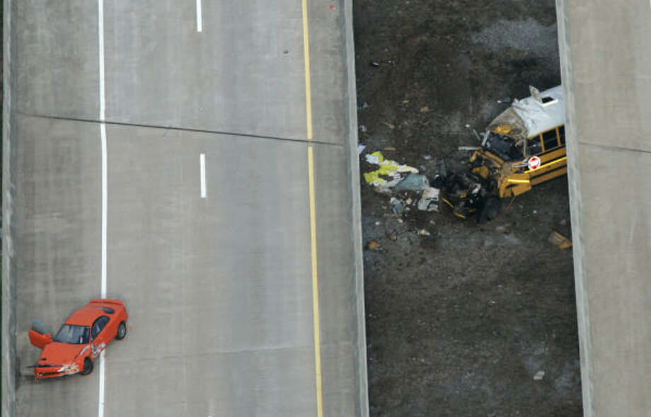A school bus fell from an overpass in Huntsville, Ala., after an accident with the car at left. Photo: ROB CARR, AP