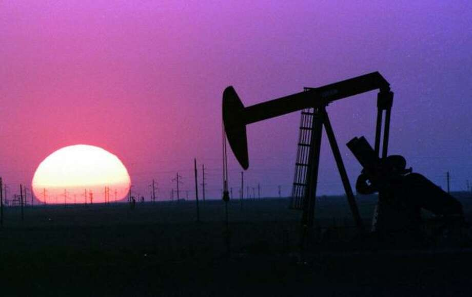 A pump jack wrests oil from the West Texas soil in 1998. Cambridge Energy Research Associates analysts say technology should allow increases in petroleum production, countering theorists who contend that global production has peaked. Photo: TIM SHARP, AP