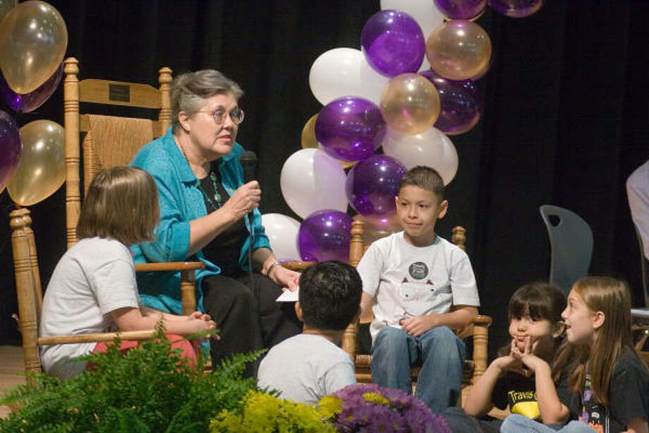 Veteran Travis Elementary School teacher Margaret Blackstone describes the history of the school and her connection to it to a group of second-graders as part of the new school's dedication ceremony. The pupils are, from left, Georgia Bartels-Newton, Esteban Herrera, Julian Cantu, Ashley Gonzales and Sadie Dill.