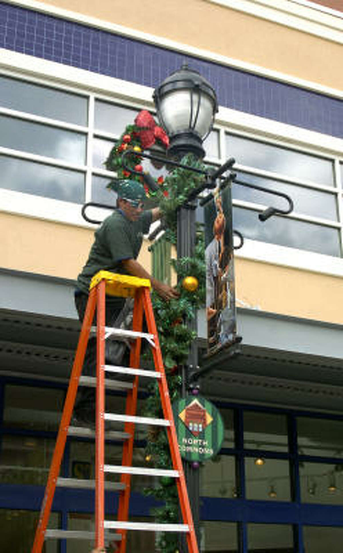Santos Gamuz puts up holiday decorations at Market Street in The Woodlands as the retail center prepares for the holiday shopping season.