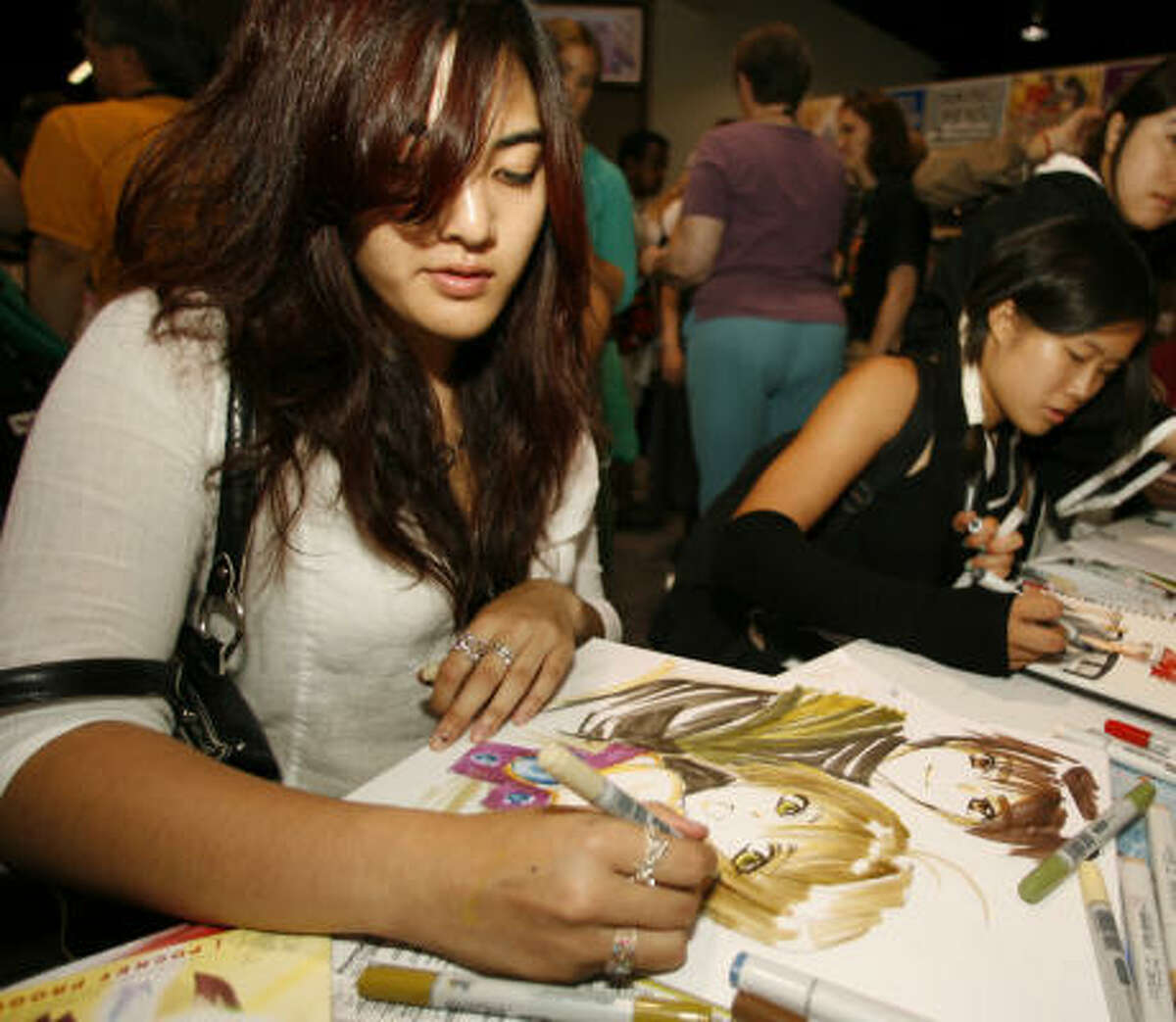 Christine Vu sits at a booth that sells manga markers and skillfully sketches a lean-lined portrait at the Anime Expo Monday, July 3, 2006, in Anaheim, Calif. Japanese anime and manga - animation and comics - are drawing a lot of attention in the United States. And, more than ever before, not just from its traditional male audience. (AP Photo/Damian Dovarganes)