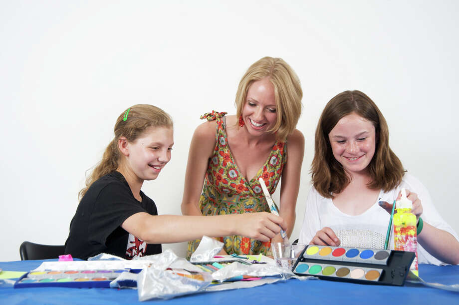 Art instructor Jessica Lynch looks on while Oliva Foster and Riley Baker work on a project during one of the center's workshops. Photo: Contributed Photo/Pamela Einarse