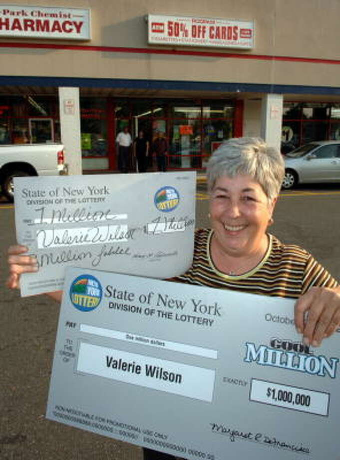 Valerie Wilson, who has just become the first person to win a million dollar scratch-off lottery prize twice, holds her mock checks given to her by the lottery agency in front of the Roopan Card shop in North Babylon, N.Y., on Friday where she purchased her most recent winning scratch-off ticket. Photo: JIM PEPPLER, AP