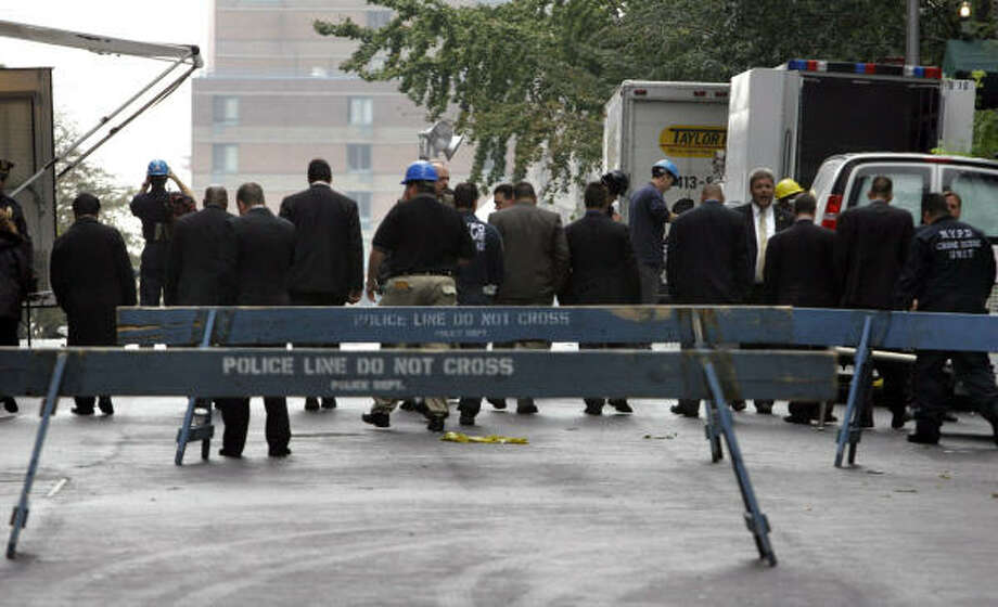 Detectives line up Thursday to canvass the street for evidence near a high-rise in New York that was struck by a small aircraft. The crash claimed the life of Yankees pitcher Cory Lidle and his flight instructor. Photo: BEBETO MATTHEWS, AP
