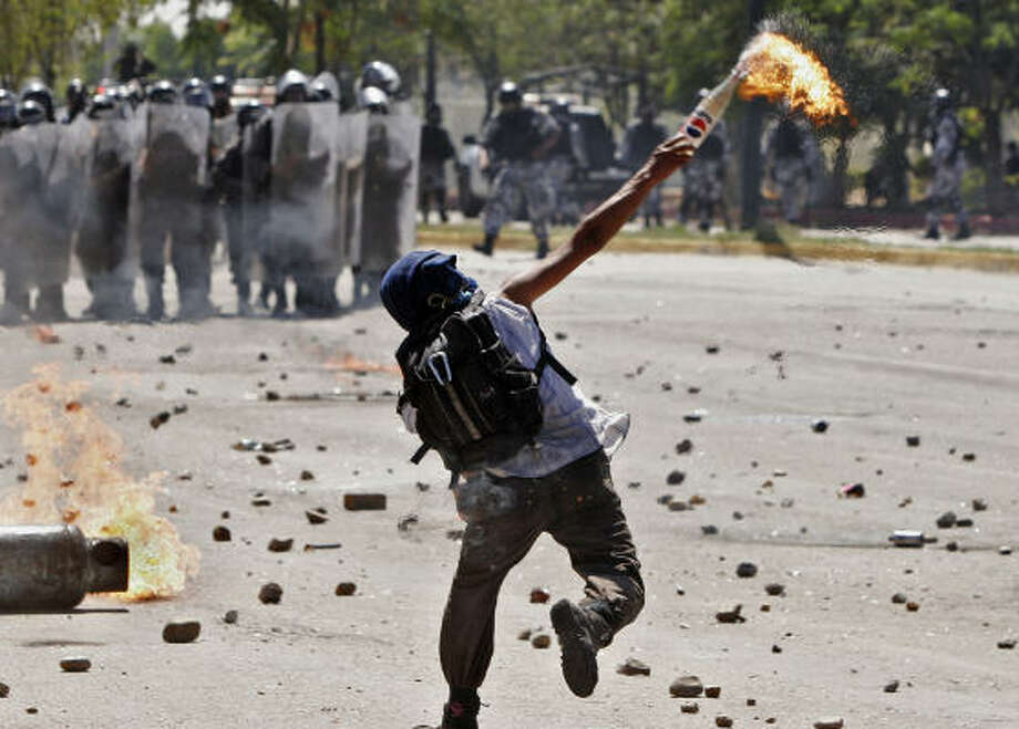 A protester hurls a Molotov cocktail at federal Mexican troops in Oaxaca on Thursday. Demonstrators are demanding the resignation of the state's governor, Ulises Ruiz, who they accuse of corruption and repression. Photo: ALFREDO ESTRELLA, AFP/Getty Images
