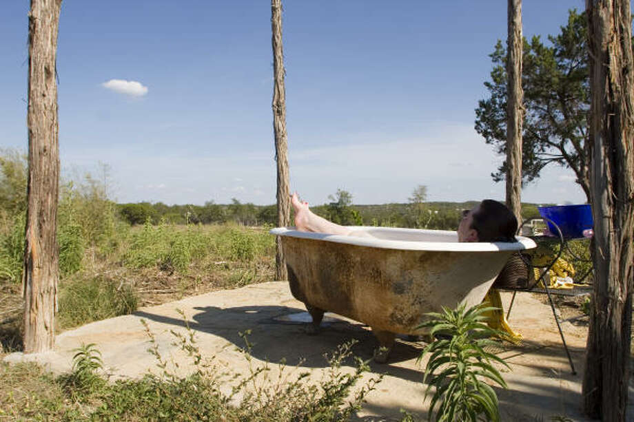 """Tina Moody of Dripping Springs not only has cut back on her water use, but takes baths in an old clawfoot tub outside her home and uses the water for irrigation. """"We just live in such denial as a culture about the limitations of our resources,"""" she said. Photo: Christina Gomez-Mira, FOR THE CHRONICLE"""