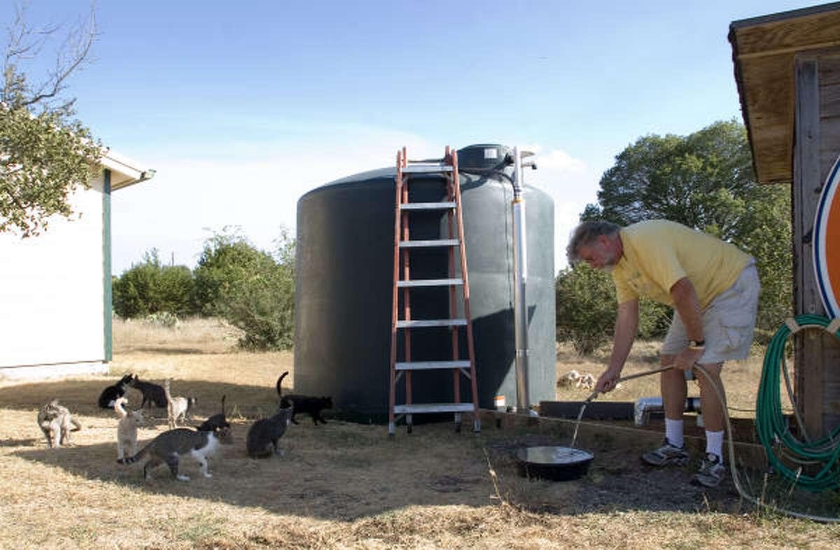 Wayland Clark gives water to his many cats in Dripping Springs. The drought has run his well dry, forcing him to have water delivered to him.
