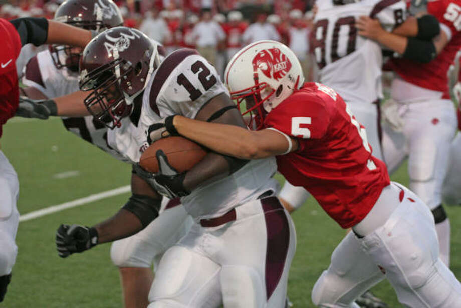 Katy's Chris Jones locks onto A&M Consolidated's C.J. Parish during the Tigers' 26-3 victory at Rhodes Stadium Friday Photo: Gary Fountain, For The Chronicle