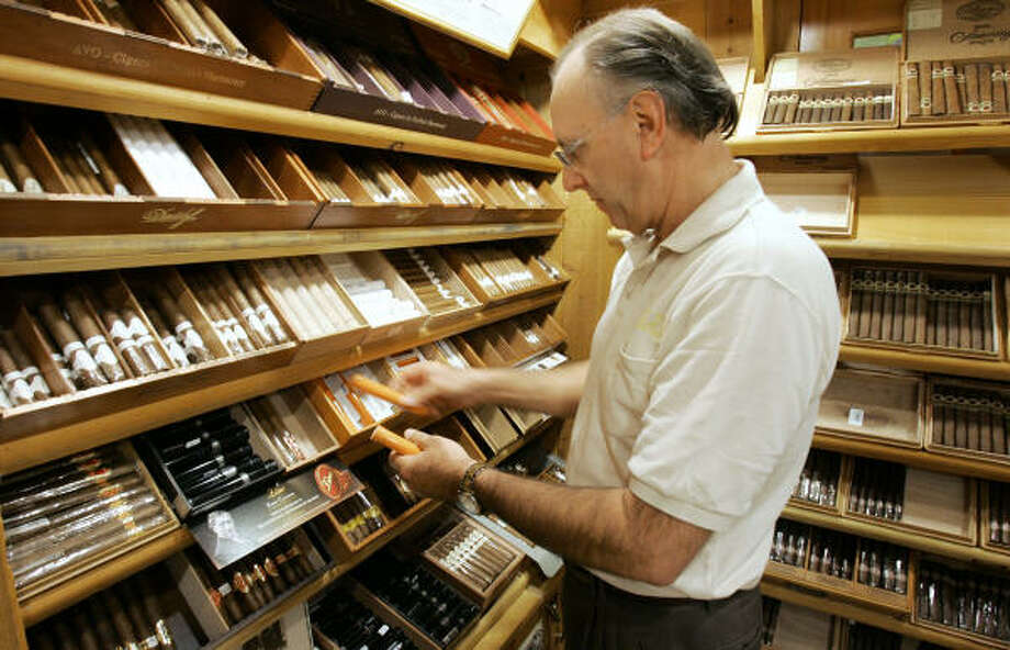 Gary Bahrenfus, manager of the Edwards Pipe and Tobacco in Tampa, arranges cigars. Sales of premium cigars is up for the first time since the 1990s. Photo: CHRIS O'MEARA, AP