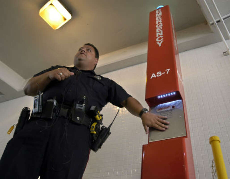 Louis Gonzalez, a Metropolitan Transit Authority police officer, shows one of the seven emergency assistance phone stations included in the new high-tech security system at the Kuykendahl Park & Ride Friday. Metro has installed 120 of the phone stations. Photo: Johnny Hanson, For The Chronicle