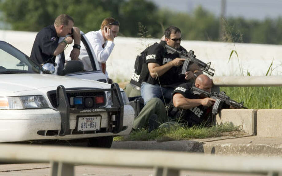 Pasadena police officers negotiate Friday with a man who led officers on a high-speed chase before crashing into a bayou along Beltway 8, north of Fairmont Parkway. Police later identified the man as Kenneth Ray Pool. Photo: BRETT COOMER, CHRONICLE