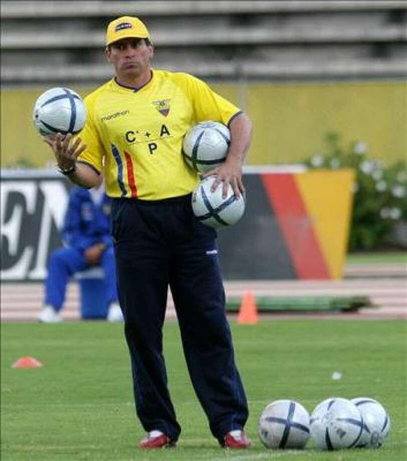 Ecuador's national football team coach, Luis Fernando Suarez, carries balls during practice at the Atahualpa Olympic Stadium, 24 March 2005 in Quito. Ecuador will meet Paraguay in a World Cup qualifying match. Photo: RODRIGO BUENDIA, AFP