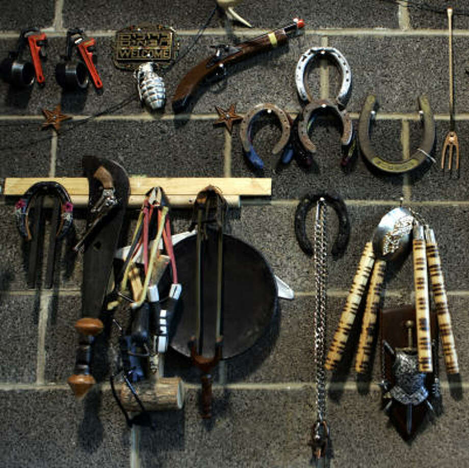 """A fake hand grenade, toy gun and a machete, items travelers had to give up at airport-security checkpoints, hang on the """"wall of fame"""" at the Pennsylvania General Services Department's surplus-property warehouse in Harrisburg, Pa. Photo: CAROLYN KASTER, AP"""