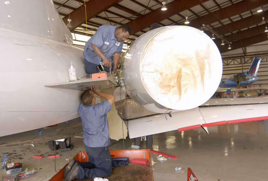 Wing Aviation aircraft technicians Kirk Newland, top, and Jose Garcia work on the rear engine mount of a Bombardier Global Express jet , which was flown from Montana to be worked on at the Wing Aviation location at the Lone Star Executive Airport in Conroe. Photo: David Hopper, For The Chronicle
