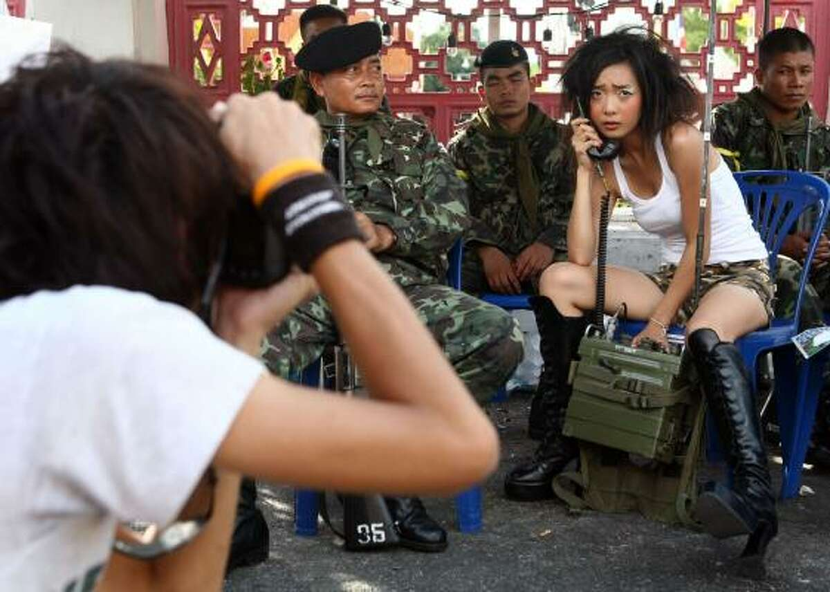 Thai fashion college students conduct a photo shoot with soldiers keeping guard near the Government House on Sept. 21 in Bangkok.