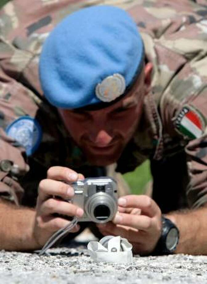 An Italian member of the U.N. interim force takes a picture of a bomblet outside of the village of Maraka, Lebanon, on Sept. 7. Photo: ALESSANDRO BIANCHI, REUTERS