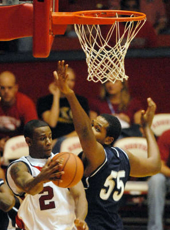 Robert Lee navigates in traffic near the basket for UH. The guard finished with 10 rebounds. Photo: Dave Rossman, For The Chronicle