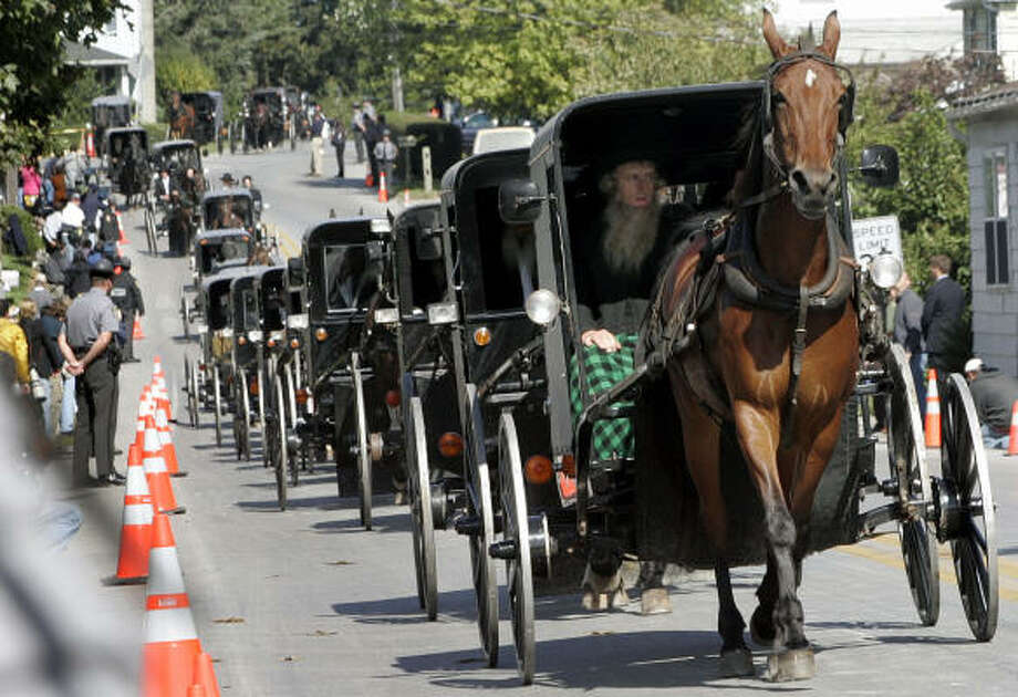 Amish buggies travel Thursday morning to Bart Amish Cemetery for the funeral of Naomi Rose Ebersol, 7, the first of the services for the five victims. The route took them by the gunman's house. Photo: MEL EVANS, AP