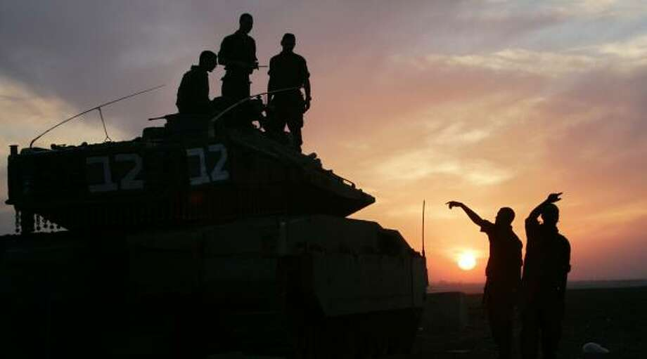 Israeli soldiers stand on top and in front of a tank at a military staging area near Kibbutz Mefalsim, just outside the northern Gaza Strip today. A cease-fire between Israel and militants in Gaza took hold and Israeli Prime Minister Ehud Olmert promised restraint in response to early Palestinian truce violations. Photo: ELIANA APONTE, REUTERS