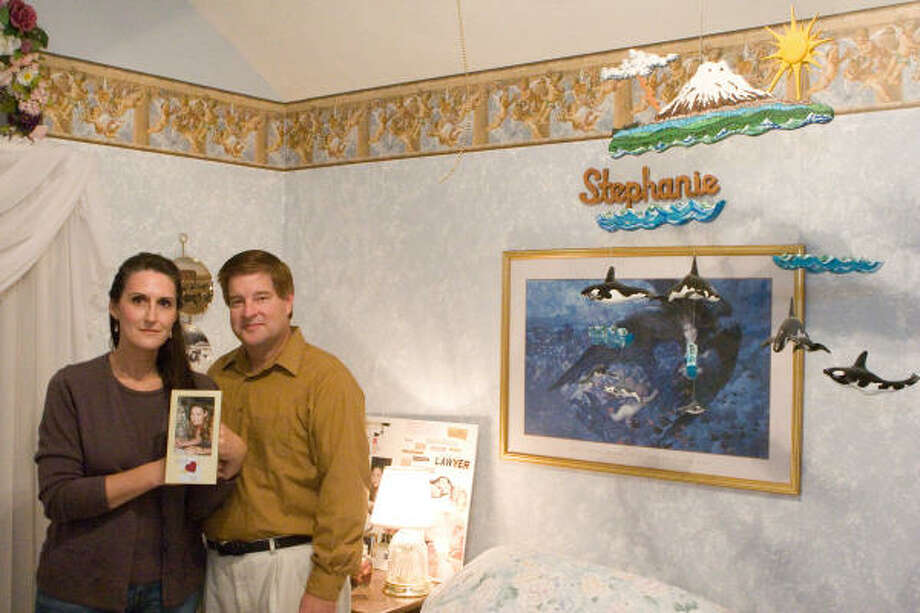 Lora Turner and Joseph Frybert of Missouri City pose with a photo of their daughter Stephanie Blaine Turner, taken just weeks before she died of heart failure at age 18. Photo: R. Clayton McKee, For The Chronicle