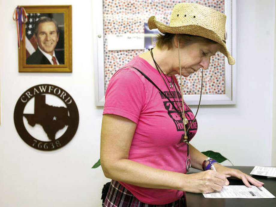 Cindy Sheehan, a vocal opponent of President Bush and the war in Iraq, fills out a voter registration card Tuesday at the post office in Crawford. Photo: DUANE A. LAVERTY, AP