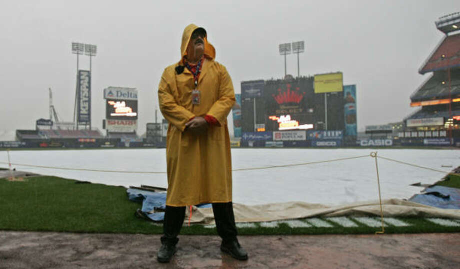Security guard Howard Broad stands in the rain at Shea Stadium before what was supposed to be Game 1 of the NLCS. Photo: CHARLES KRUPA, AP