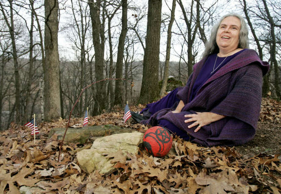 Selena Fox, a Wiccan priestess and founder of Circle Sanctuary, sits alongside the buried remains of a Korean War soldier near Barneveld, Wis. She and others sued the U.S. Department of Veterans Affairs over its ban on graveside pentacles at national cemeteries. Photo: ANDY MANIS, AP