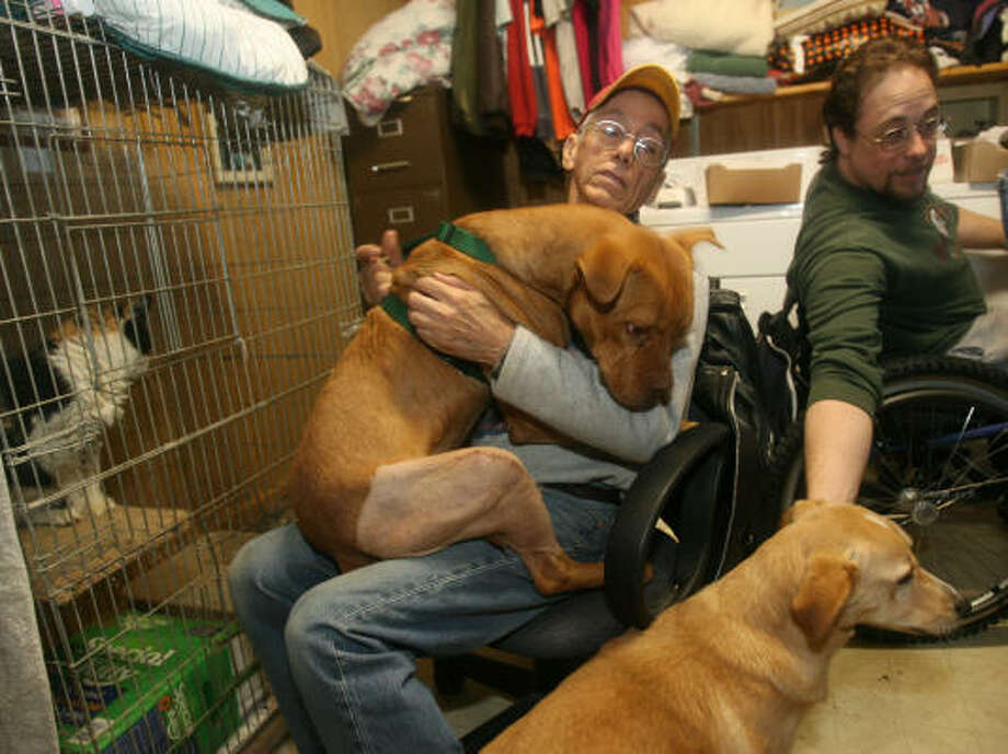 Carlos Arreola embraces Mikey at the no-kill Little Woman Home for Animals shelter office near Huntsville. Photo: Mayra Beltran, Chronicle