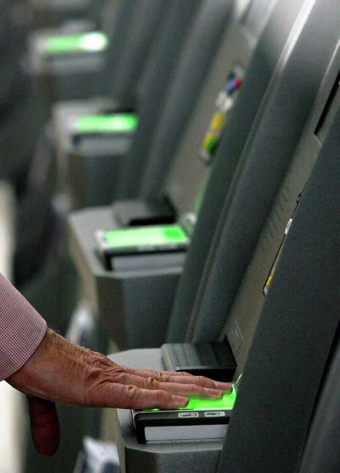 Airline passenger Clint Folsom checks in using a Global Entry kiosk at George Bush Intercontinental Airport Wednesday, Aug. 10, 2011, in Houston. Global Entry is a U.S. Customs and Border Protection (CBP) program that allows pre-approved clearance to passengers to bypass long lines when returning to the United States. Passengers must have a background check and an interview before they are eligible to enroll. ( Cody Duty / Houston Chronicle ) Photo: Cody Duty, Staff / © 2011 Houston Chronicle