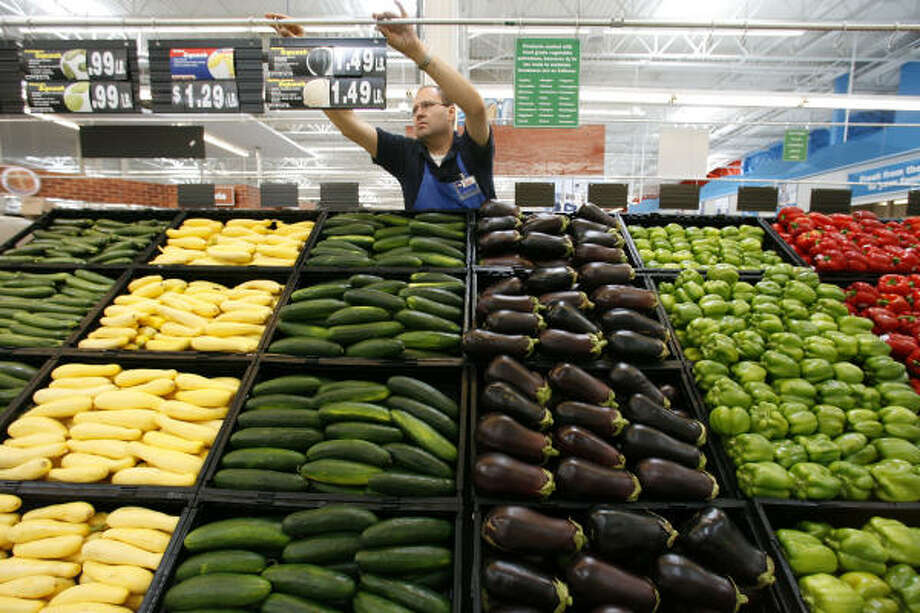 Carlos Llinas installs pricing signs in the produce section of the H-E-B Plus store in the Katy Grand Parkway area. The new store has more types of produce than a typical H-E-B. Photo: Billy Smith II, Chronicle