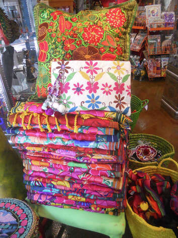 This Consuela bag, $69, Guatemalan pillow cover, $38-$48, and table runners, $165, are all at Tienda al Garza. JENNIFER RODRIGUEZ / SPECIAL TO THE EXPRESS-NEWS