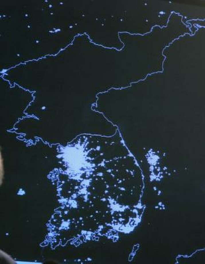 A satellite image of the Korean peninsula at night showing the lights of South Korea and the relative darkness of North Korea is displayed at a Pentagon briefing in Washington on Wednesday. Photo: JASON REED, Reuters