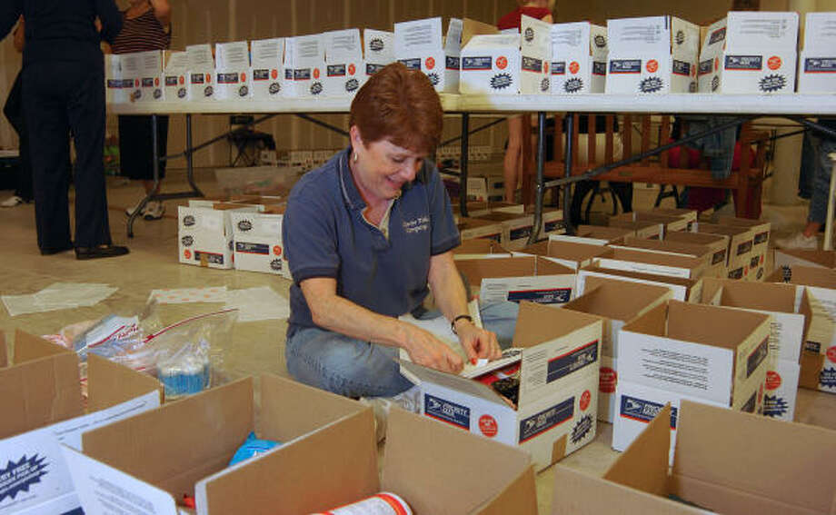 Cathy Cobb of The Woodlands puts packing labels on one of the boxes being shipped to Iraq as part of the Montgomery County Chapter of Women's Council of Realtors Holiday for Heroes. Photo: David Hopper, For The Chronicle