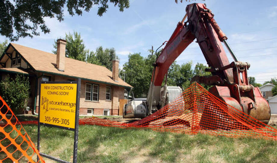 Construction equipment marks a Denver area where bungalows are being cleared to make room for larger homes. Photo: DAVID ZALUBOWSKI, AP