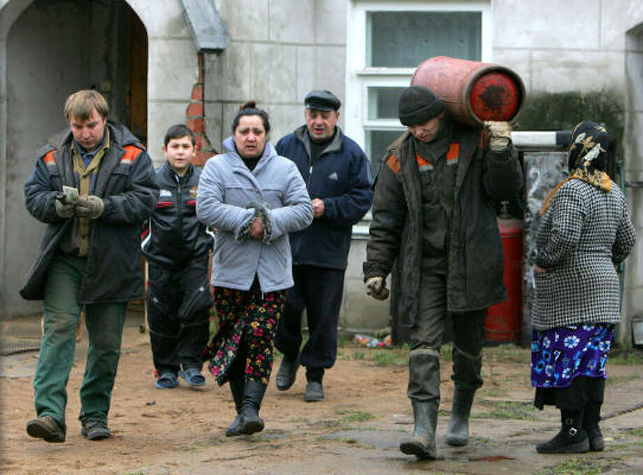 People in the village of Biazyn, Belarus, buy natural gas cylinders on Wednesday. Russia's Gazprom is demanding that Belarus double its payments for gas next year and give it a 50 percent stake in the country's distribution system. Gazprom is threatening a Jan. 1 supply cutoff. Photo: VIKTOR DRACHEV, AFP/Getty Images