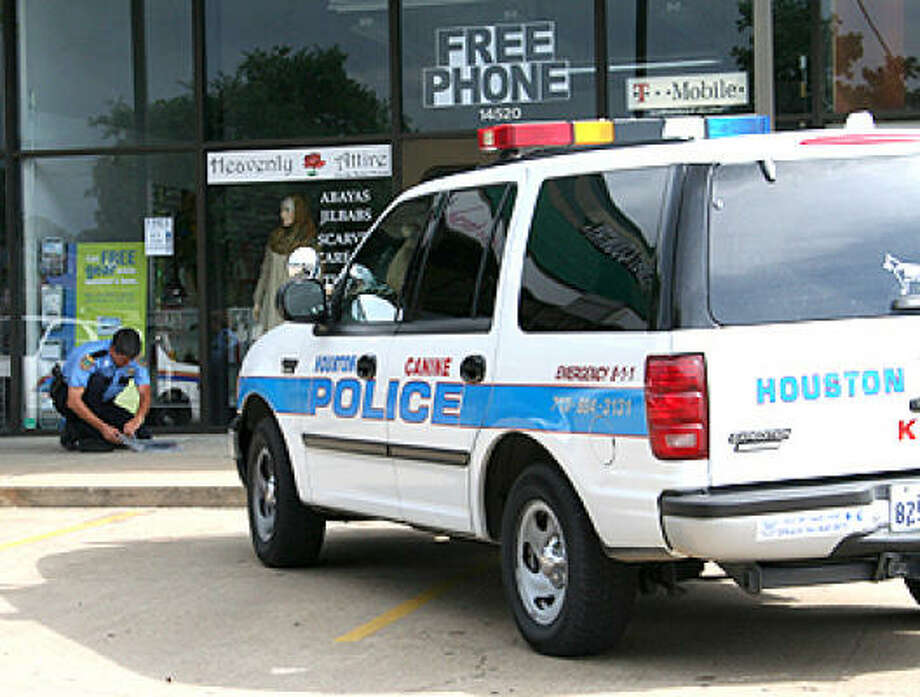A Houston police officer examines evidence outside the cell-phone store this morning, while a K-9 officer, with his police dog inside an SUV,  prepares to leave the scene. Photo: Chronicle